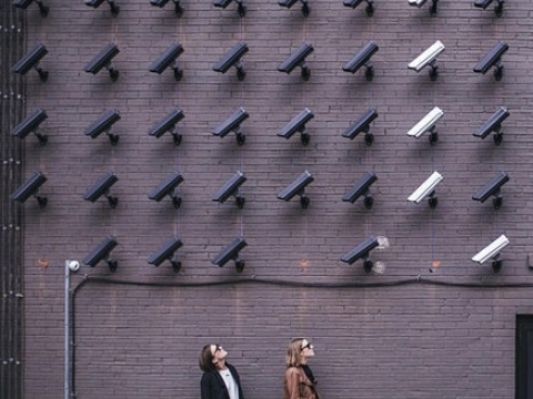 Two women looking up at surveillance cameras.
