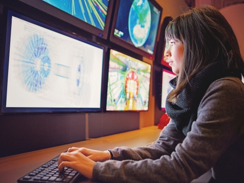Woman looking into multiple monitor screens.