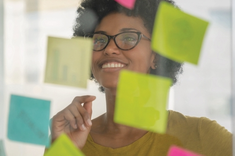 woman smiling in front of post it notes